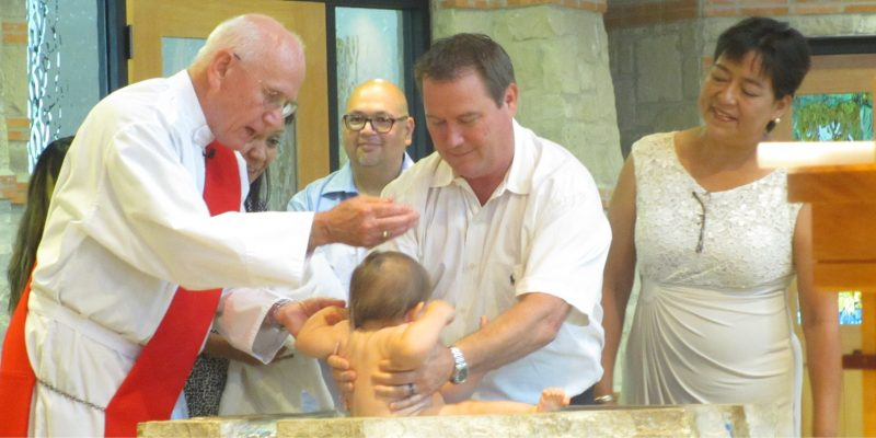 deacon Tom baptizing baby